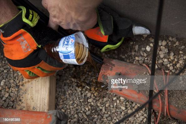 Lubricant is poured into an underground tube to help reduce friction on fiber optic internet cables during installation in Minneapolis Minnesota US...