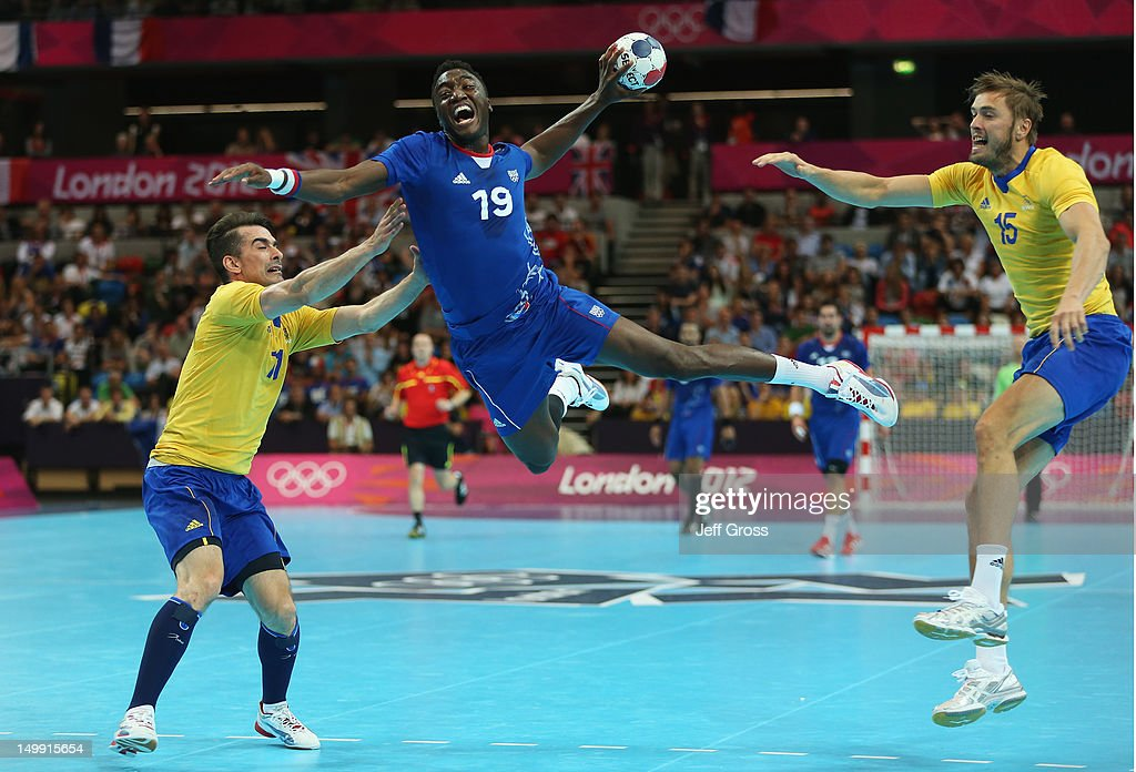 Luc Abalo of France jumps to shoot while Dalibor Doder and Jonas Larholm of Sweden can just watch on during the Men's Handball preliminaries group A...