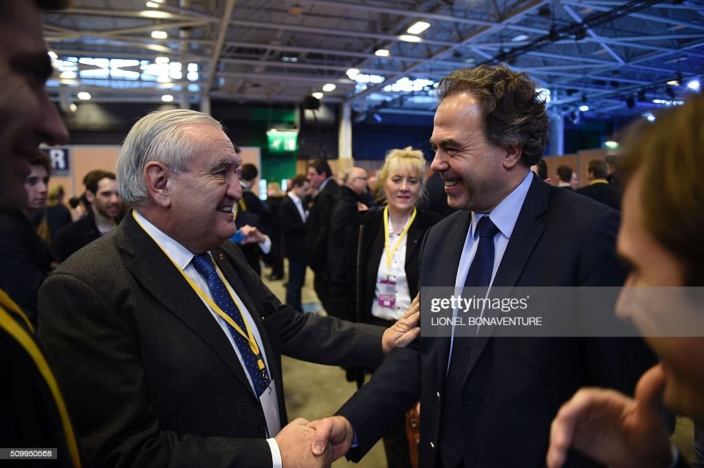 Luc Chatel (R), special advisor of Les Republicains (LR) right-wing party president, shakes hands with LR party member and Former Prime Minister of France Jean-Pierre Raffarin (L) during the LR National Council on February 13, 2016 in Paris. AFP PHOTO / LIONEL BONAVENTURE / AFP / LIONEL BONAVENTURE
