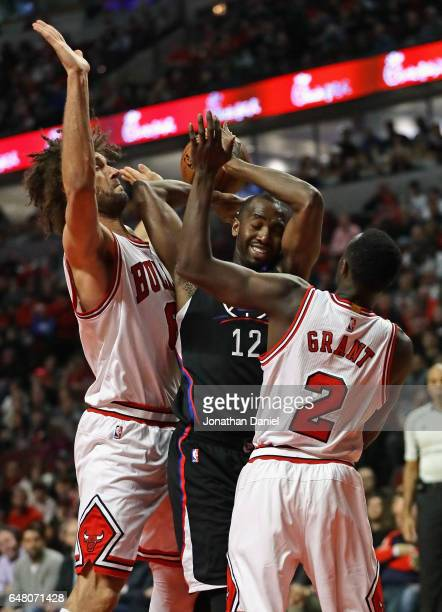 Luc Mbah a Moute of the LA Clippers tries to get off a shot between Robin Lopez and Jerian Grant of the Chicago Bulls at the United Center on March 4...