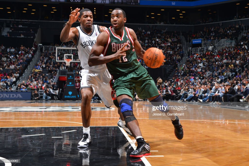 Luc Richard Mbah a Moute #12 of the Milwaukee Bucks drives to the basket against Joe Johnson #7 of the Brooklyn Nets during the game at the Barclays Center on December 9, 2012 in Brooklyn, New York.