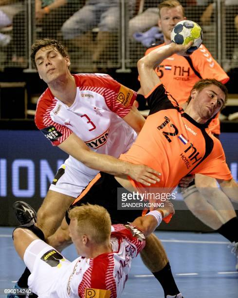 Luc Steins of The Netherlands prepares to throw the ball past Niclas Kirkelokke of Denmark during their EC qualification handball match in Almere on...