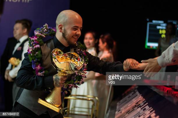 Luca Brecel of Belgium celebrates with his trophy after the final match against Shaun Murphy of England on day seven of Evergrande 2017 World Snooker...