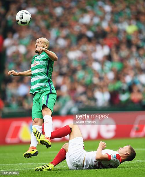 Luca Caldirola of Bremen is challenged by Afred Finnbogson of Augsburg during the Bundesliga match between Werder Bremen and FC Augsburg at...