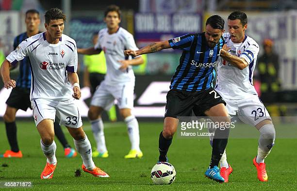 Luca Cigarini of Atalanta BC is challenged by Manuel Pasqual of ACF Fiorentina during the Serie A match between Atalanta BC and ACF Fiorentina at...