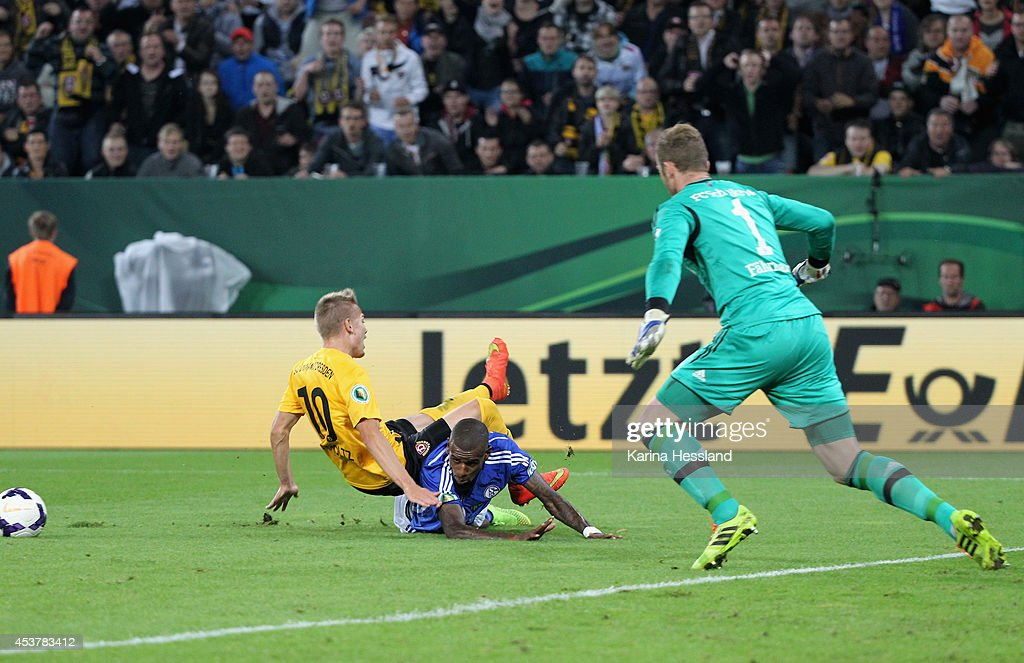 Luca Duerholtz of Dresden is fouled, winning a penalty kick, by <a gi-track='captionPersonalityLinkClicked' href=/galleries/search?phrase=Felipe+Santana&family=editorial&specificpeople=5422021 ng-click='$event.stopPropagation()'>Felipe Santana</a> of Schalke 04 during the DFB Cup between SG Dynamo Dresden and FC Schalke 04 at Gluecksgas-Stadion on August 18, 2014 in Dresden, Germany.