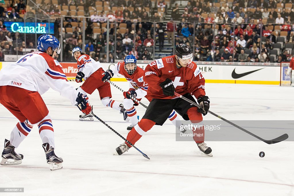 Luca Hischier #13 of Switzerland moves the puck against Lukas Klok #6 of Czech Republic during the 2015 IIHF World Junior Championship on December 27, 2014 at the Air Canada Centre in Toronto, Ontario, Canada.