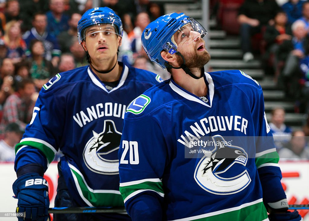 Luca Sbisa and Chris Higgins of the Vancouver Canucks skate to the bench during their NHL game against the Edmonton Oilers at Rogers Arena October 11...