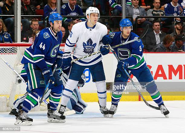 Luca Sbisa and Erik Gudbranson of the Vancouver Canucks keep James van Riemsdyk of the Toronto Maple Leafs in check during their NHL game at Rogers...