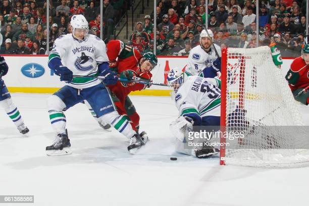 Luca Sbisa and goalie Richard Bachman of the Vancouver Canucks defend their goal against Zach Parise of the Minnesota Wild during the game on March...