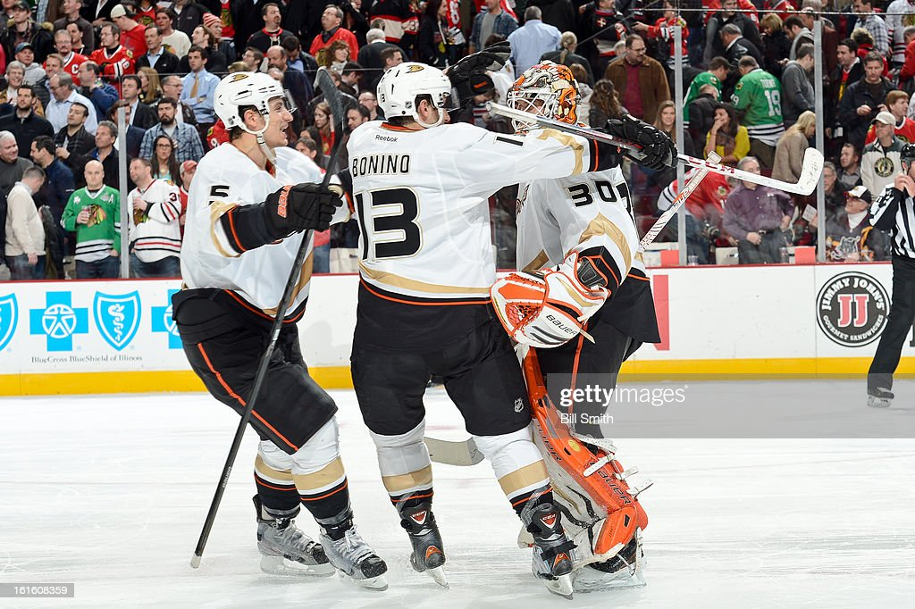 Luca Sbisa #5 and Nick Bonino #13 of the Anaheim Ducks hug teammate goalie Viktor Fasth #30 after the Ducks defeated the Chicago Blackhawks in overtime during the NHL game on February 12, 2013 at the United Center in Chicago, Illinois.