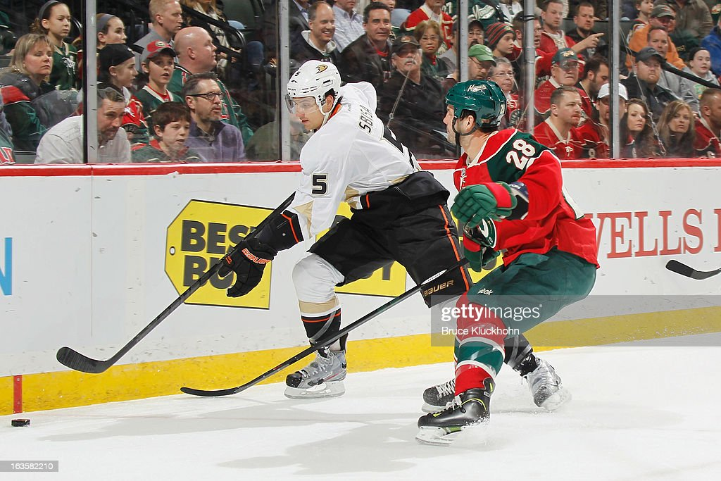 <a gi-track='captionPersonalityLinkClicked' href=/galleries/search?phrase=Luca+Sbisa&family=editorial&specificpeople=4893043 ng-click='$event.stopPropagation()'>Luca Sbisa</a> #5 of the Anaheim Ducks skates with the puck while <a gi-track='captionPersonalityLinkClicked' href=/galleries/search?phrase=Zenon+Konopka&family=editorial&specificpeople=2105876 ng-click='$event.stopPropagation()'>Zenon Konopka</a> #28 of the Minnesota Wild defends during the game on March 12, 2013 at the Xcel Energy Center in Saint Paul, Minnesota.