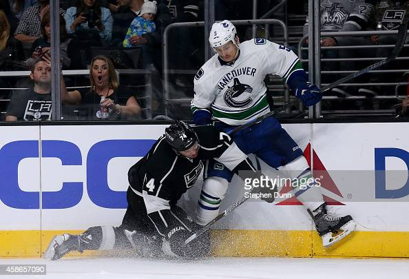 Luca Sbisa of the Vancouver Canucks and Dwight King of the Los Angeles Kings crash into the boards at Staples Center on November 8 2014 in Los...
