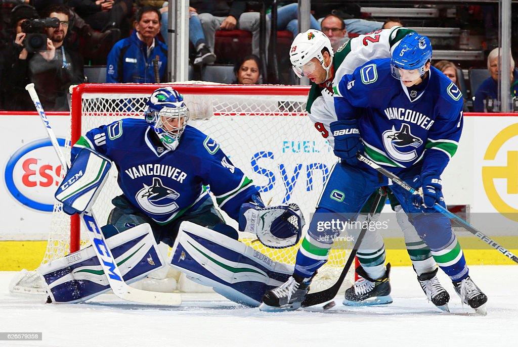 Luca Sbisa #5 of the Vancouver Canucks and Jason Pominville #29 of the Minnesota Wild look at the rebound after Ryan Miller #30 of the Vancouver Canucks makes a save during their NHL game at Rogers Arena November 29, 2016 in Vancouver, British Columbia, Canada. Vancouver won 5-4.
