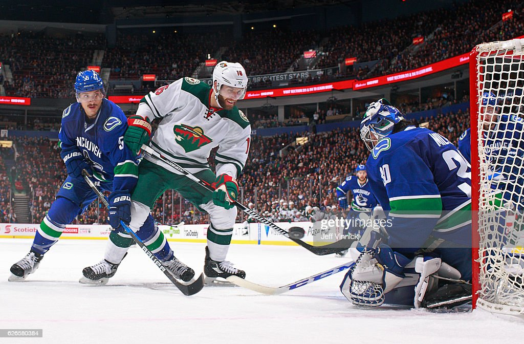 Luca Sbisa #5 of the Vancouver Canucks and Jason Zucker #16 of the Minnesota Wild look on as Ryan Miller #30 of the Vancouver Canucks makes a save during their NHL game at Rogers Arena November 29, 2016 in Vancouver, British Columbia, Canada. Vancouver won 5-4.