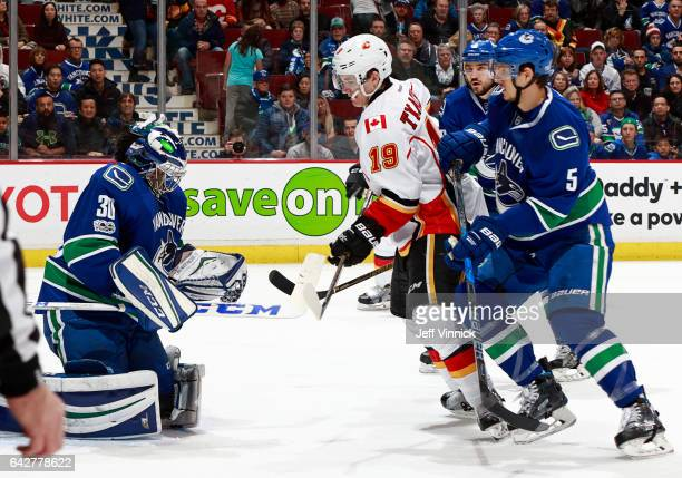 Luca Sbisa of the Vancouver Canucks and Matthew Tkachuk of the Calgary Flames look on as Ryan Miller cover the puck during their NHL game at Rogers...