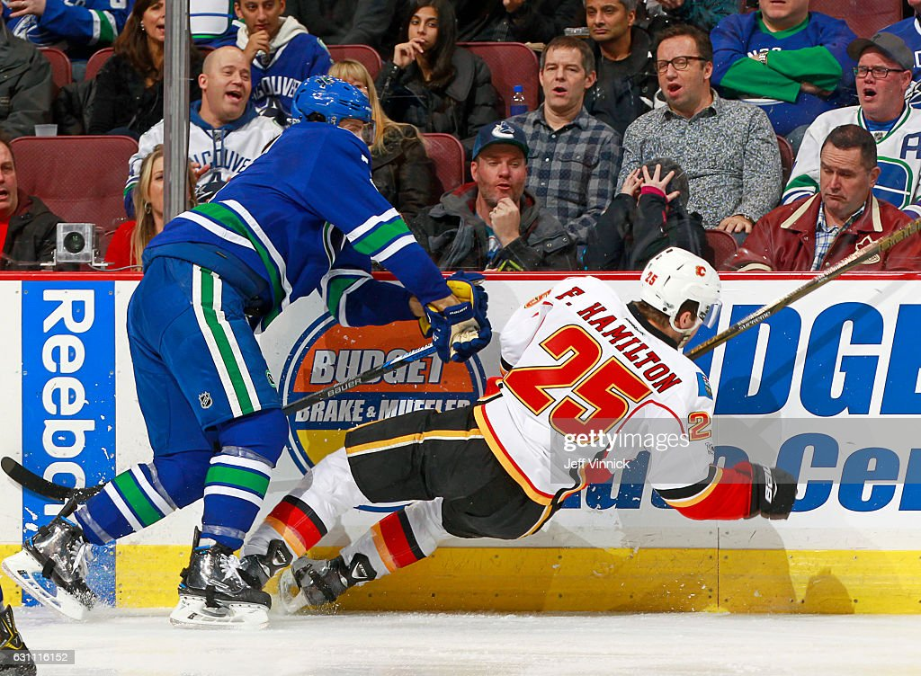 Luca Sbisa #5 of the Vancouver Canucks checks Freddie Hamilton #25 of the Calgary Flames during their NHL game at Rogers Arena January 6, 2017 in Vancouver, British Columbia, Canada. Vancouver won 4-2.
