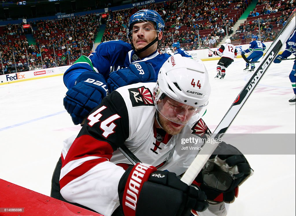 Luca Sbisa of the Vancouver Canucks checks Kevin Connauton of the Arizona Coyotes during their NHL game at Rogers Arena March 9 2016 in Vancouver...
