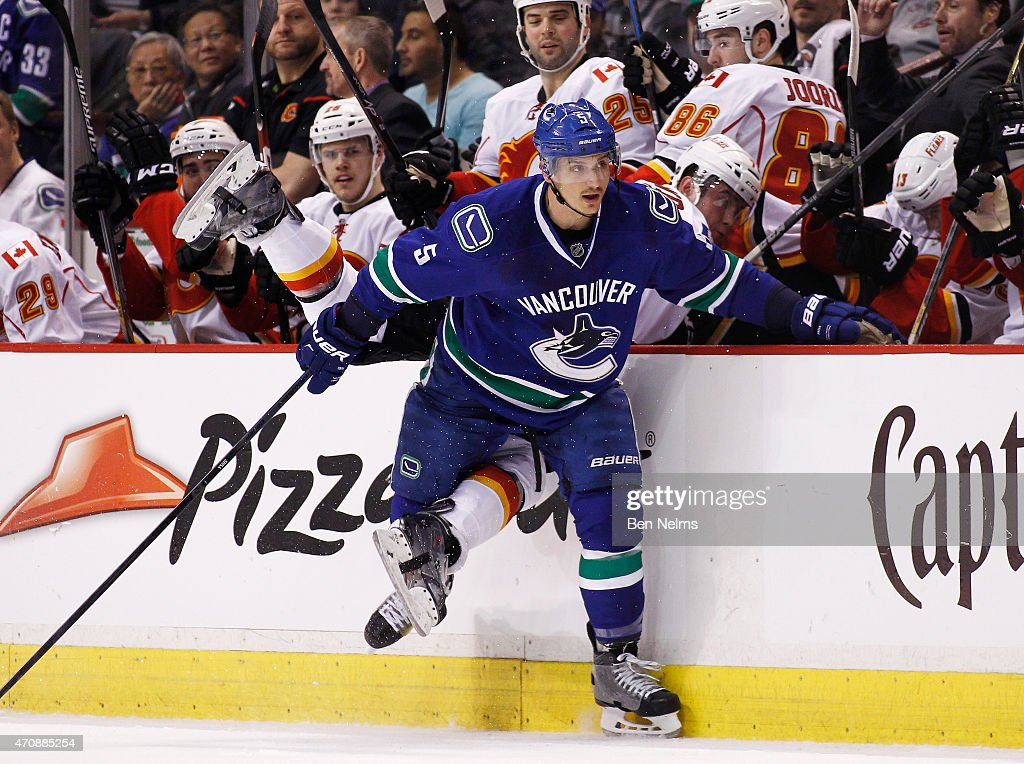 Luca Sbisa of the Vancouver Canucks checks Michael Ferland of the Calgary Flames during Game Five of the Western Conference Quarterfinals during the...