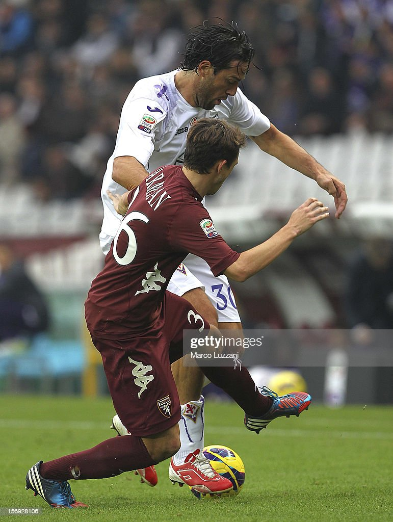 Luca Toni of ACF Fiorentina competes for the ball with Matteo Darmian of Torino FC during the Serie A match between Torino FC and ACF Fiorentina at Stadio Olimpico di Torino on November 25, 2012 in Turin, Italy.