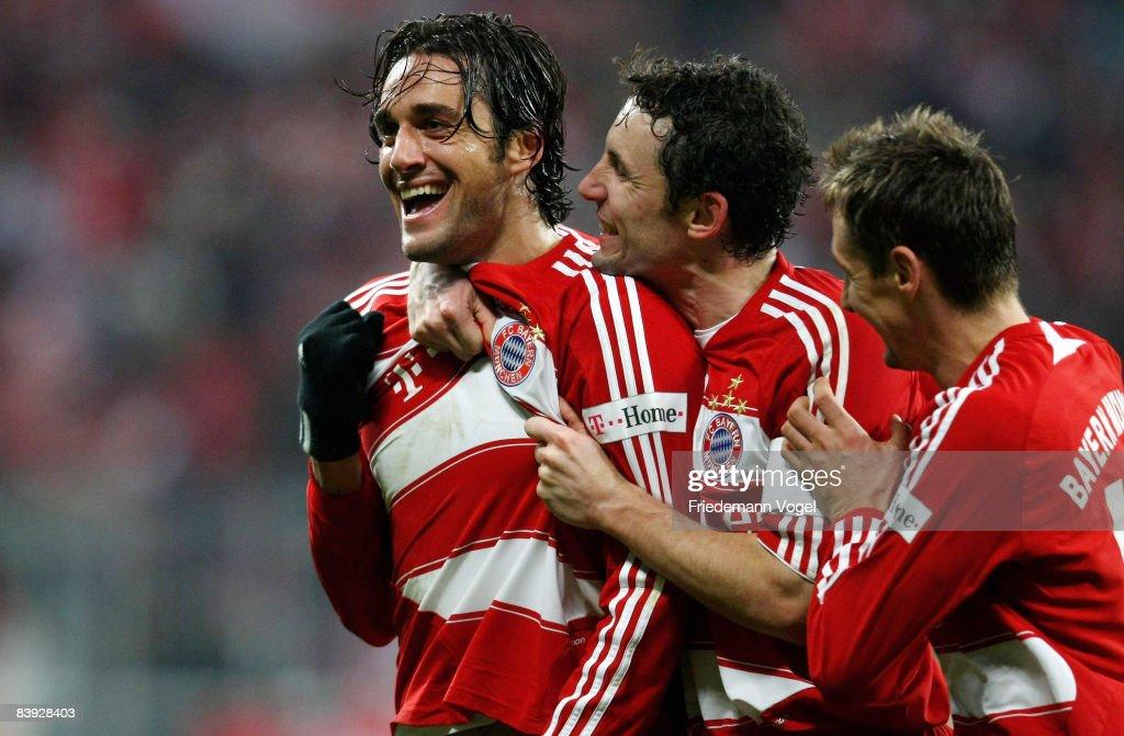 Luca Toni of Bayern celebrates after scoring the winning goal with Mark van Bommel and Miroslav Klose during the Bundesliga match between Bayern...