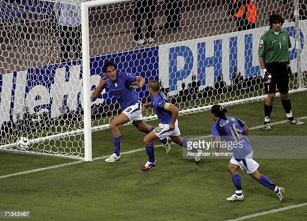 Luca Toni of Italy celebrates with teammates after scoring his team's second goal during the FIFA World Cup Germany 2006 Quarterfinal match between...