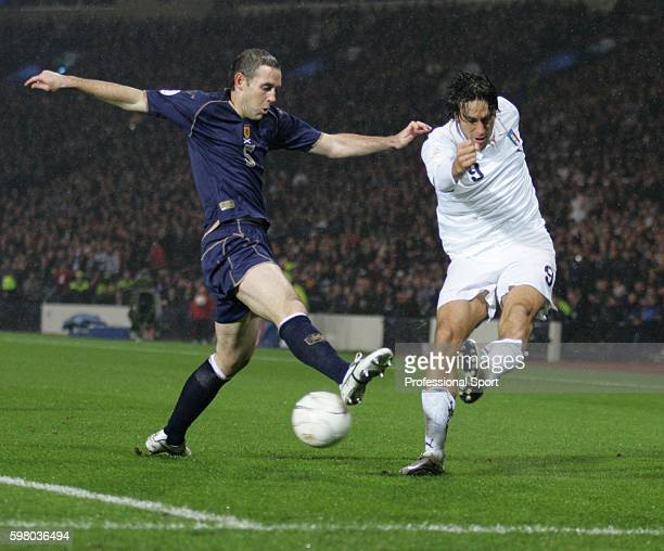 Luca Toni of Italy crosses the ball past Scotland defender David Weir during the UEFA Euro 2008 Qualifying match between Scotland and Italy at...