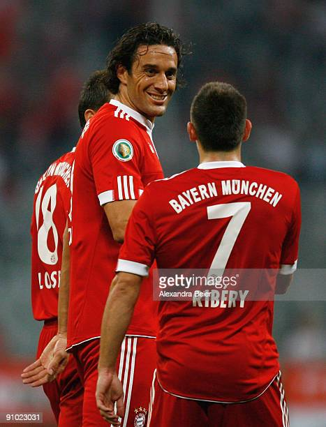 Luca Toni of Muenchen smiles as he talks to his teammate Franck Ribery during the DFB Cup second round match between FC Bayern Muenchen and RotWeiss...