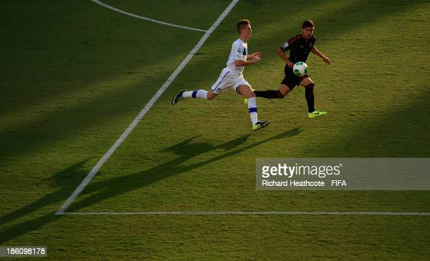 Luca Vido of Italy chases down Pedro Teran of Mexico during the FIFA U17 World Cup UAE 2013 Round of 16 match between Italy and Mexico at the Mohamed...