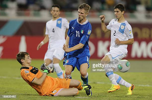 Luca Vido of Italy is tackled by Thiago Cardozo of Uruguay during the Group B FIFA U17 World Cup match between Italy and Uruguay at Ras Al Khaimah...