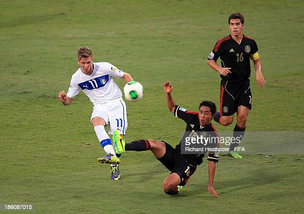 Luca Vido of Italy shoots past Omar Govea of Mexico during the FIFA U17 World Cup UAE 2013 Round of 16 match between Italy and Mexico at the Mohamed...