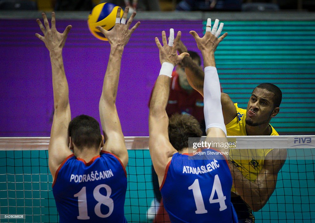 Lucarelli of Brazil spikes the ball as Marko Podrascanin and Aleksandar Atanasijevic of Serbia attempts to block during the match between Brasil and...