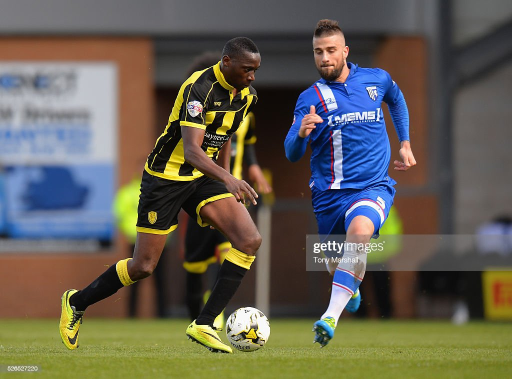 Lucas Akins of Burton Albion is challenged by Max Ehmer of Gillingham during the Sky Bet League One match between Burton Albion and Gillingham at Pirelli Stadium on April 30, 2016 in Burton-upon-Trent, England.