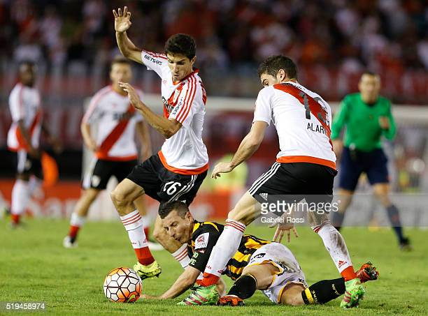 Lucas Alario and Ignacio Fernandez of River Plate fight for the ball with Pablo Escobar of The Strongest during a match between River Plate and The...