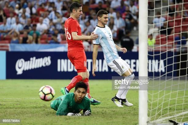 Lucas Alario of Argentina shoots past Izwan Mahbud of Singapore during the International Test match between Argentina and Singapore at National...