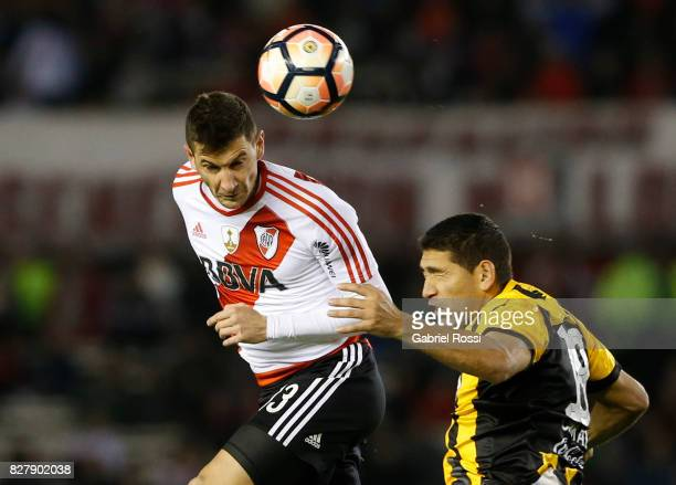 Lucas Alario of River Plate fights for the ball with Luis Alberto Cabral of Guarani during a second leg match between River Plate and Guarani as part...