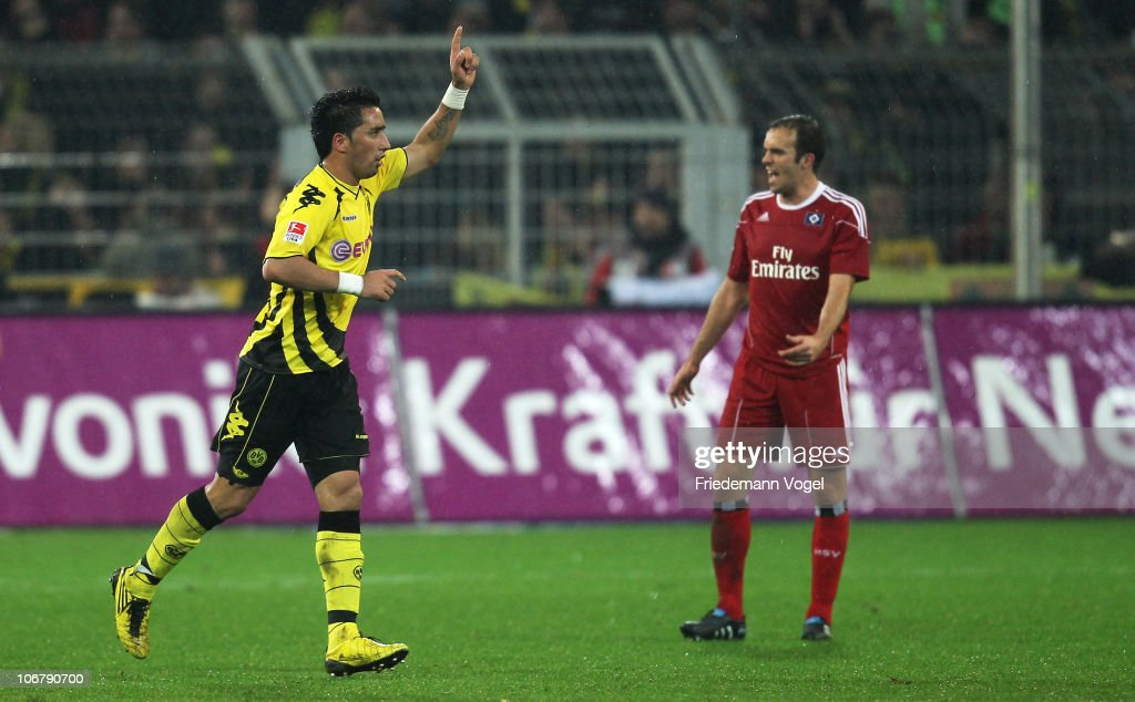 Lucas Barrios of Dortmund celebrates scoring the second goal and Joris Mathijsen looks dejected during the Bundesliga match between Borussia Dortmund and Hamburger SV at Signal Iduna Park on November 12, 2010 in Dortmund, Germany.
