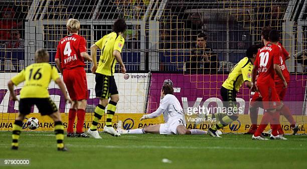 Lucas Barrios of Dortmund scores his team's first goal against Rene Adler of Leverkusen during the Bundesliga match between Borussia Dortmund and...