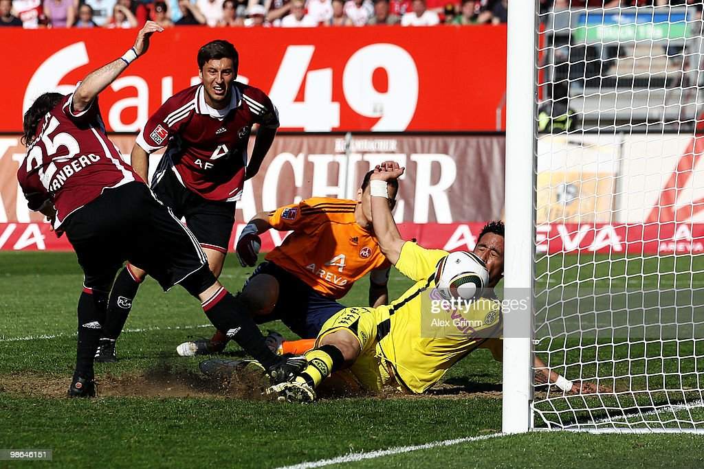 Lucas Barrios of Dortmund scores his team's third goal against goalkeeper Raphael Schaefer Dominic Maroh and Javier Pinola of Nuernberg during the...