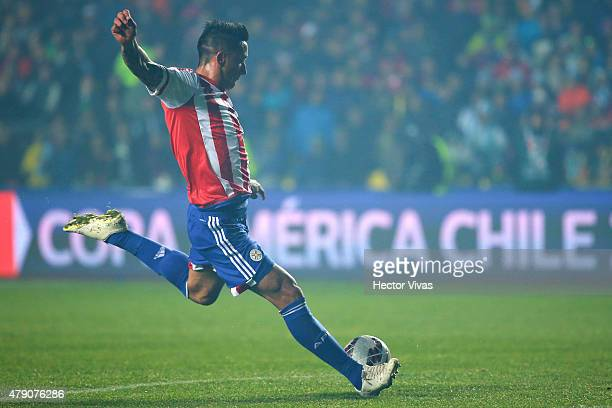 Lucas Barrios of Paraguay shoots to score the first goal of his team during the 2015 Copa America Chile Semi Final match between Argentina and...
