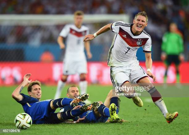 Lucas Biglia and Javier Mascherano of Argentina challenge Bastian Schweinsteiger of Germany during the 2014 FIFA World Cup Brazil Final match between...