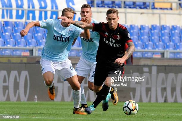 Lucas Biglia of AC Milan compete for the ball with Lucas Leiva of SS Lazio during the Serie A match between SS Lazio and AC Milan at Stadio Olimpico...