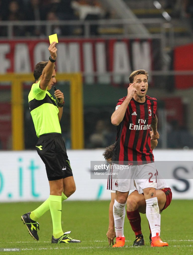 Lucas Biglia (R) of AC Milan receives the yellow card from referee Luca Banti during the Serie A match between AC Milan and AS Roma at Stadio Giuseppe Meazza on October 1, 2017 in Milan, Italy.