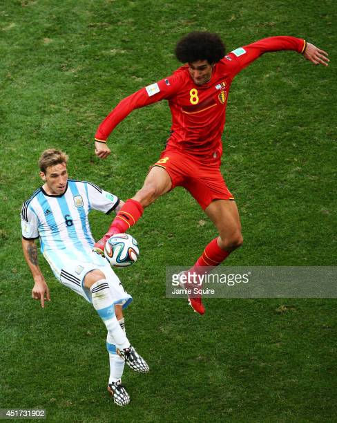 Lucas Biglia of Argentina and Marouane Fellaini of Belgium compete for the ball during the 2014 FIFA World Cup Brazil Quarter Final match between...