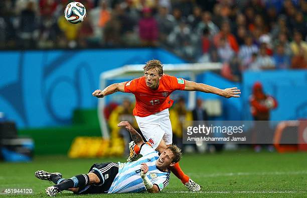 Lucas Biglia of Argentina in action against Joel Veltman of Netherlands during the 2014 FIFA World Cup Brazil Semi Final match between the...