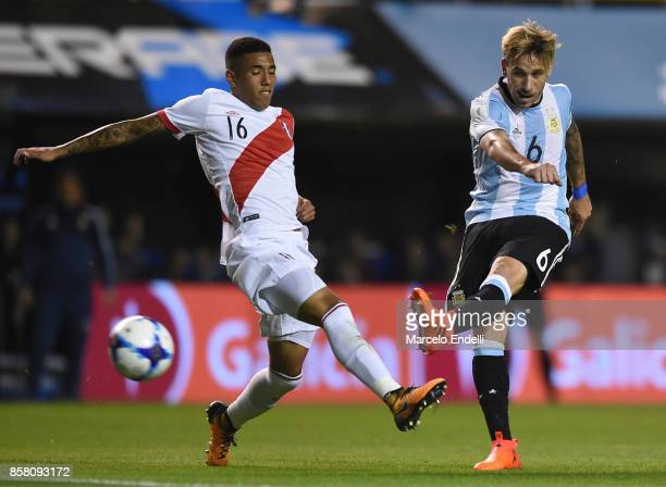 Lucas Biglia of Argentina kicks the ball as Sergio Peña of Peru tries to block the shot during a match between Argentina and Peru as part of FIFA...