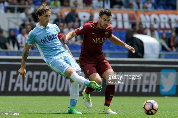 Lucas Biglia of SS Lazio compete for the ball with Kevin Strootman of AS Roma during the Serie A match between AS Roma and SS Lazio at Stadio...