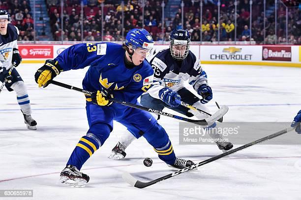 Lucas Carlsson of Team Sweden skates the puck against Eeli Tolvanen of Team Finland during the 2017 IIHF World Junior Championship preliminary round...