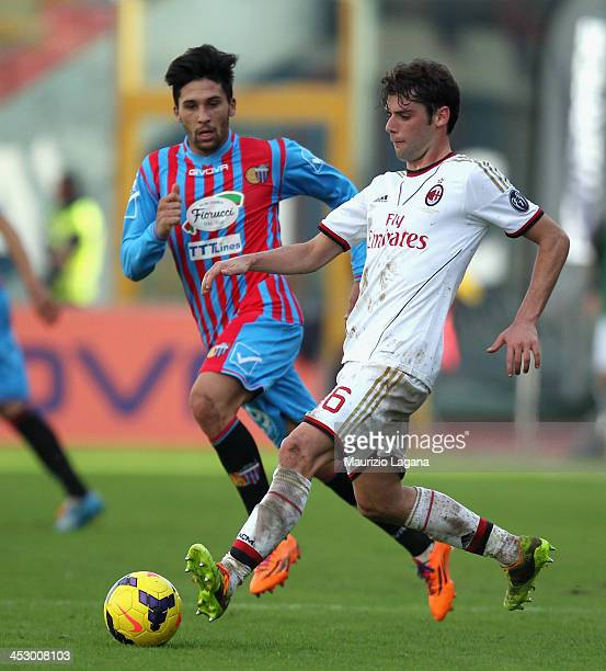 Lucas Castro of Catania competes for the ball with Andrea Poli of Milan during the Serie A match between Calcio Catania and AC Milan at Stadio Angelo...