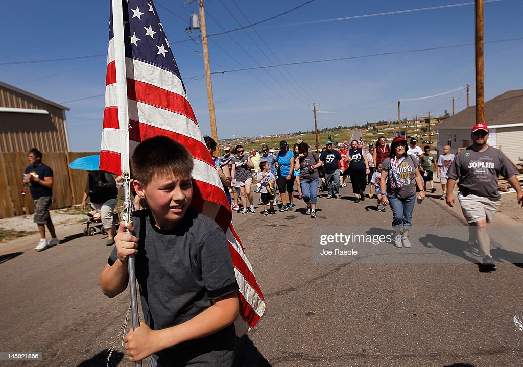 Lucas Danner carries an American flag as he and other people walk together during a city sponsored Walk of Unity through the area that was ravaged by a massive tornado one year ago today on May 22, 2012 in Joplin, Missouri. The EF-5 tornado devastated the area leaving behind a path of destruction along with 161 deaths and hundreds of injuries, but one year later there are signs that the town is beginning to recover.